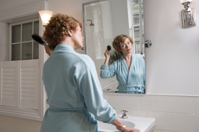 woman looking in mirror, brushing hair