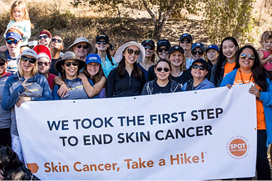 Group of people holding a sign for AAD's Skin Cancer, Take a Hike!™