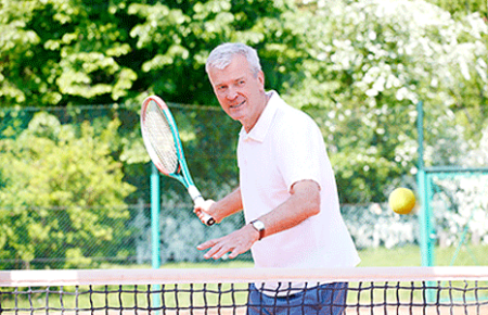 Older gentleman playing tennis