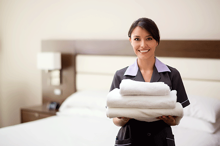 Hotel maid holding clean towels