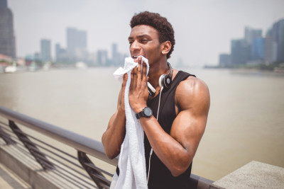 Man wiping face after exercise