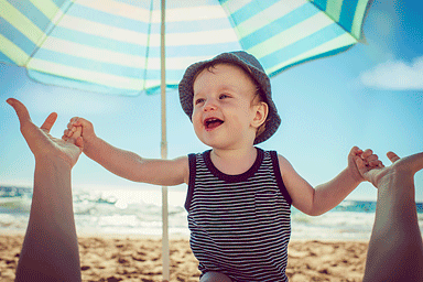 Baby with mother on the beach under an umbrella for sun protection