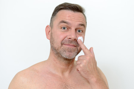 Middle aged man putting cream on his face