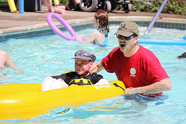 Counselor playing with camp kids in pool