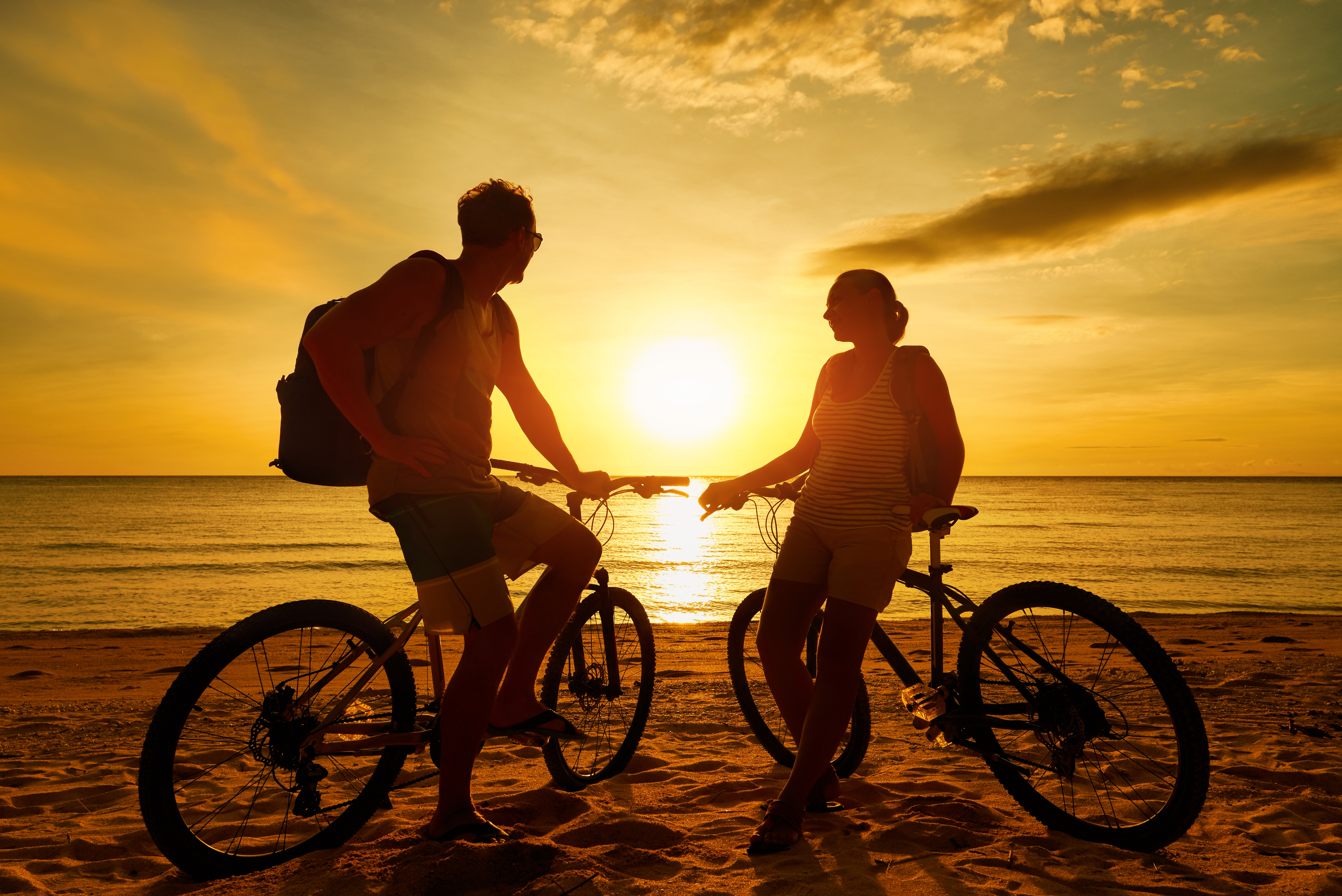 A couple with their bicycles watching sunset
