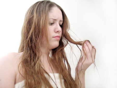 woman examining her dry hair