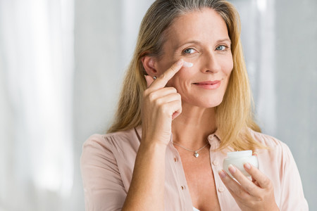 A woman in her 50s applying cream on her face