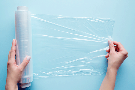 Woman's hand using a roll of plastic wrap