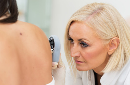 Female dermatologist examining female patient's skin with dermascope, carefully looking for signs of skin cancer