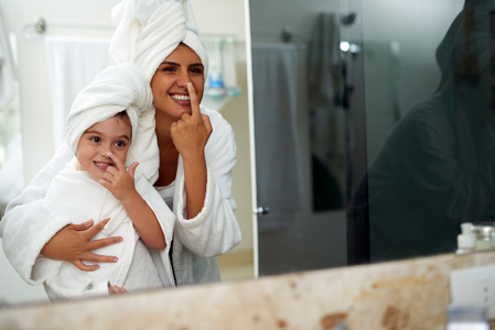 Mother and daughter towel-drying their hair
