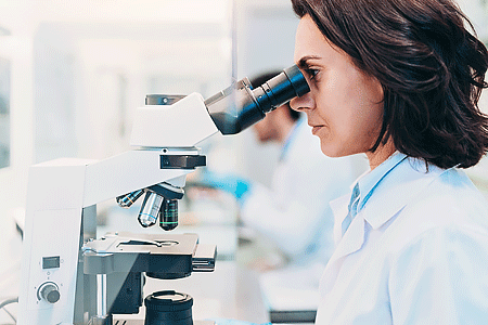 Close-up of a female doctor looking through a microscope