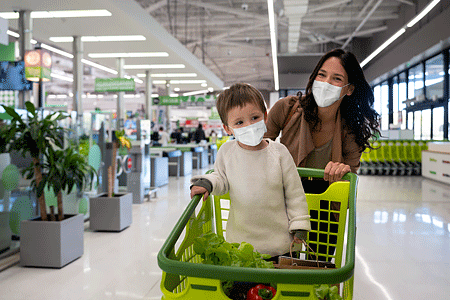 Mother grocery shopping with her toddler at the supermarket wearing face masks and pushing the cart.