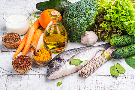Fresh vegetables, a fish, and other healthy foods