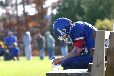 Football player sits on the sideline bench