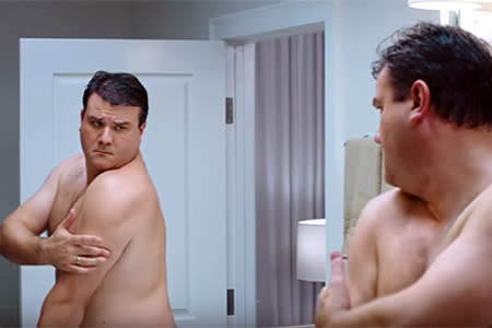 Man checking skin on the back of his body in the mirror