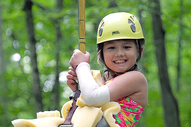 Camp Discovery attendee smiling while zip-lining