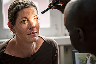 Woman getting eye exam for eczema