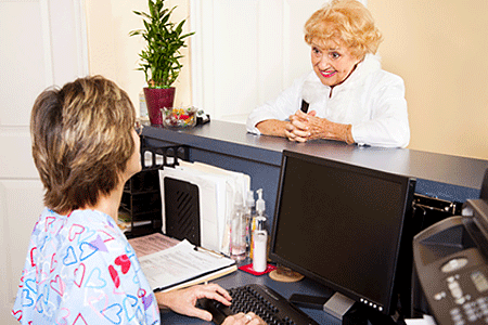 Woman at medical office speaking with receptionist at desk