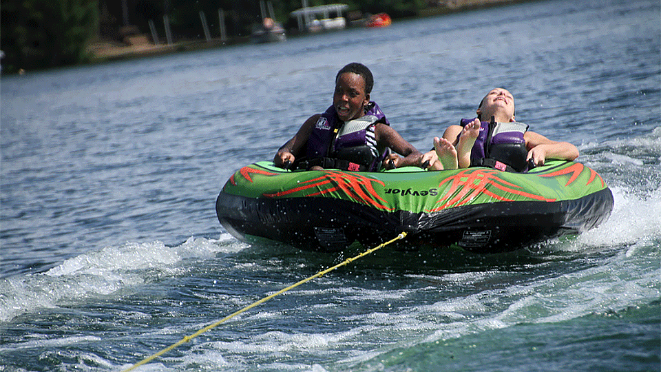 Children being pulled by a boat in an inner tube