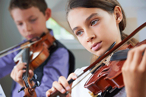 Two young children playing violin.