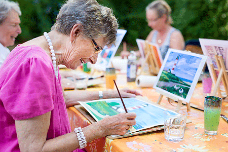 Side view of a happy senior woman smiling while drawing outdoors together with a group of retired women
