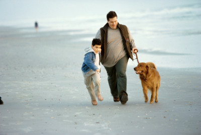 father, son, dog on beach