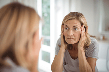 Senior woman looking in mirror pulling on sagging skin on her face