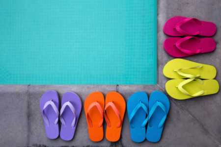Brightly colored flip flops on edge of pool