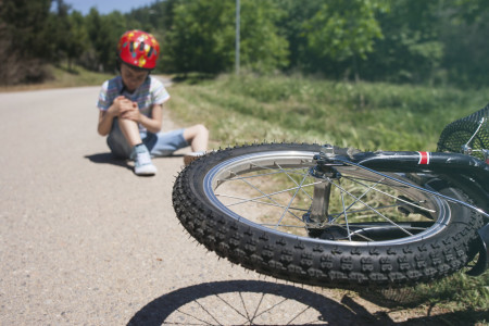 Boy sitting hurt on pavement after a bicycle accident