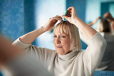 Senior woman applying serum to scalp to prevent hair loss, looking at mirror in bathroom