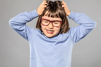 Irritated young girl scratching head due to head lice