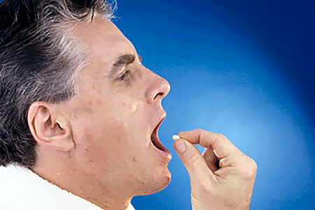 Man putting a pill in his mouth