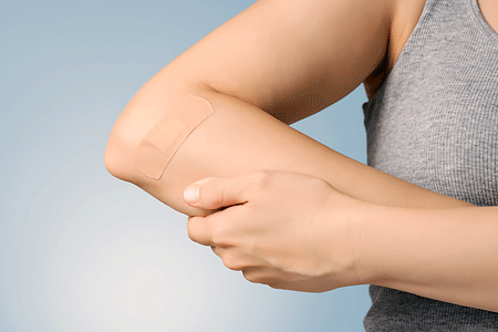 Female arm with adhesive bandage on blue background