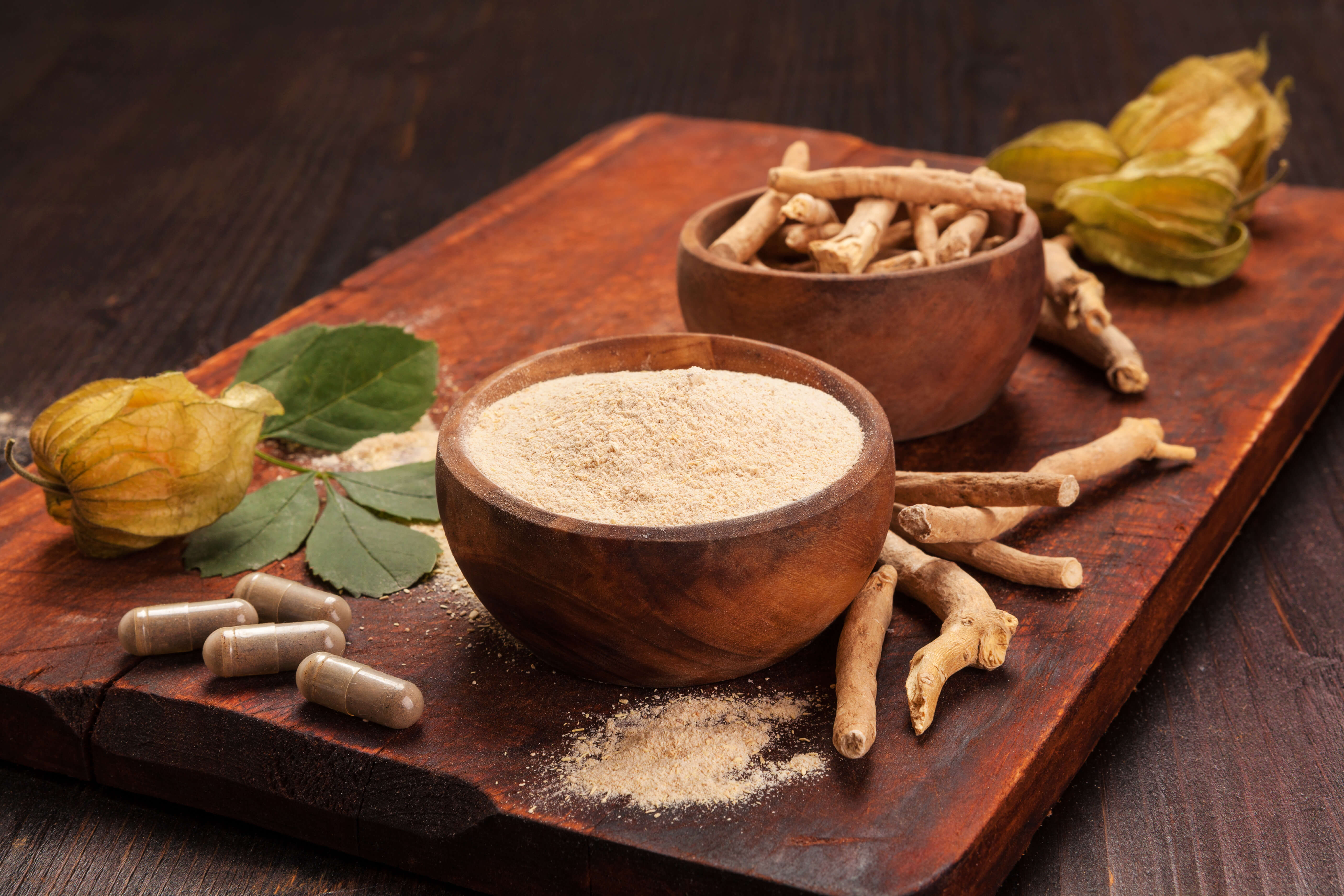 Ashwagandha for Dogs: A wooden table topped with Ashwagandha root, Ashwagandha powder, and Ashwagandha capsules.