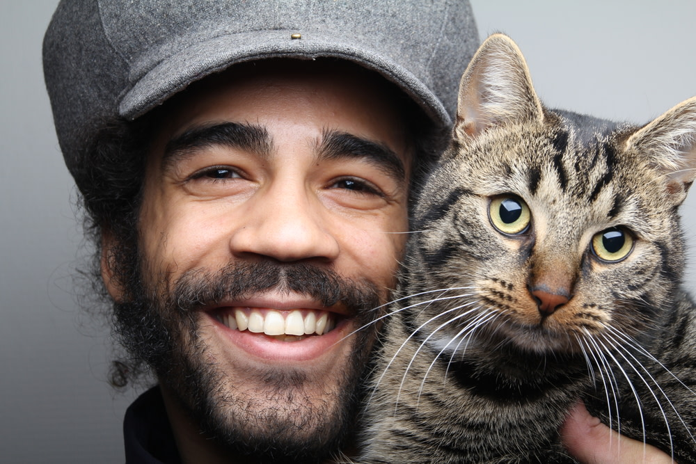 smiling pet owner with his happy cat