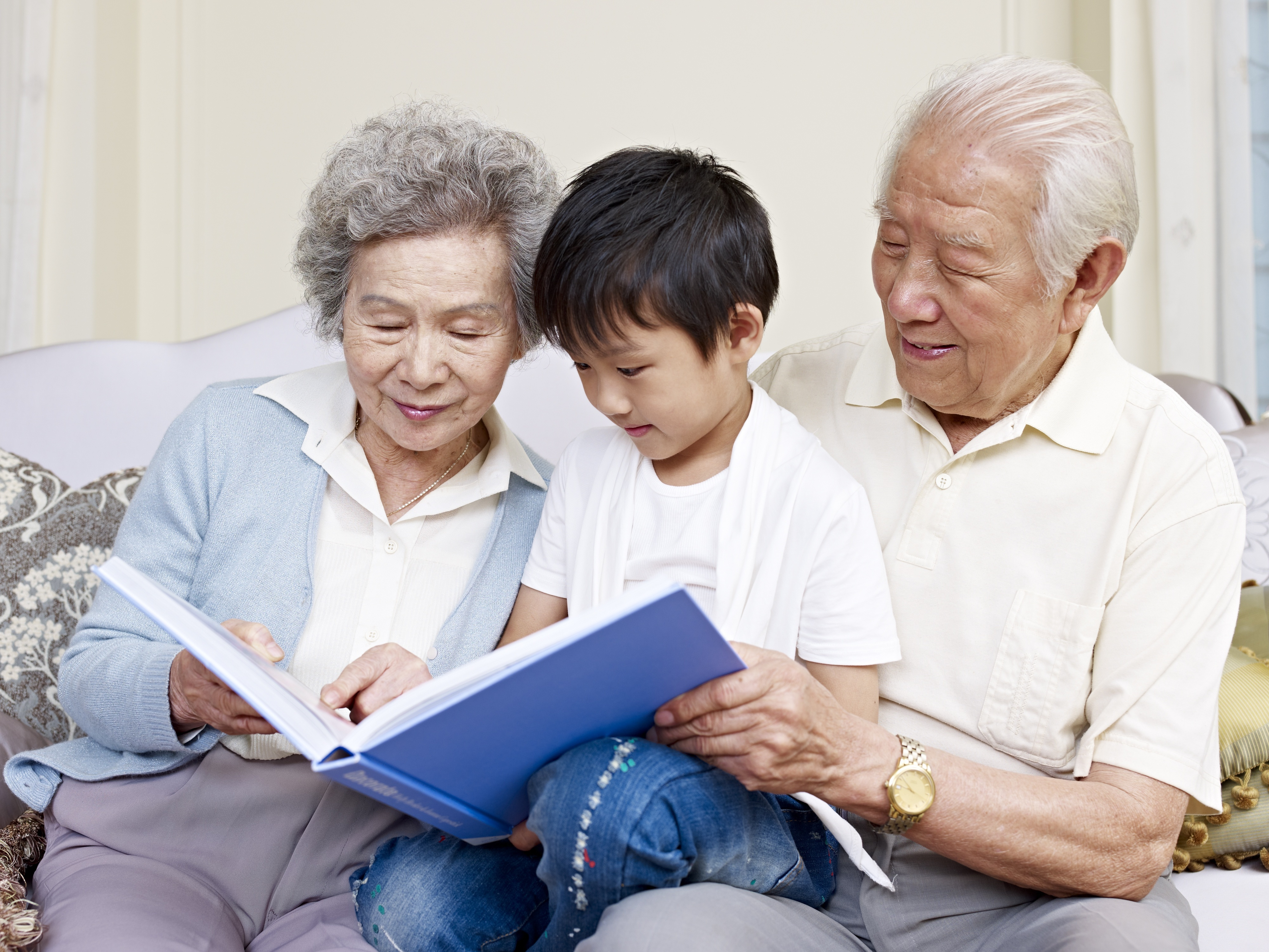 Grandparents and grandson reading a book together