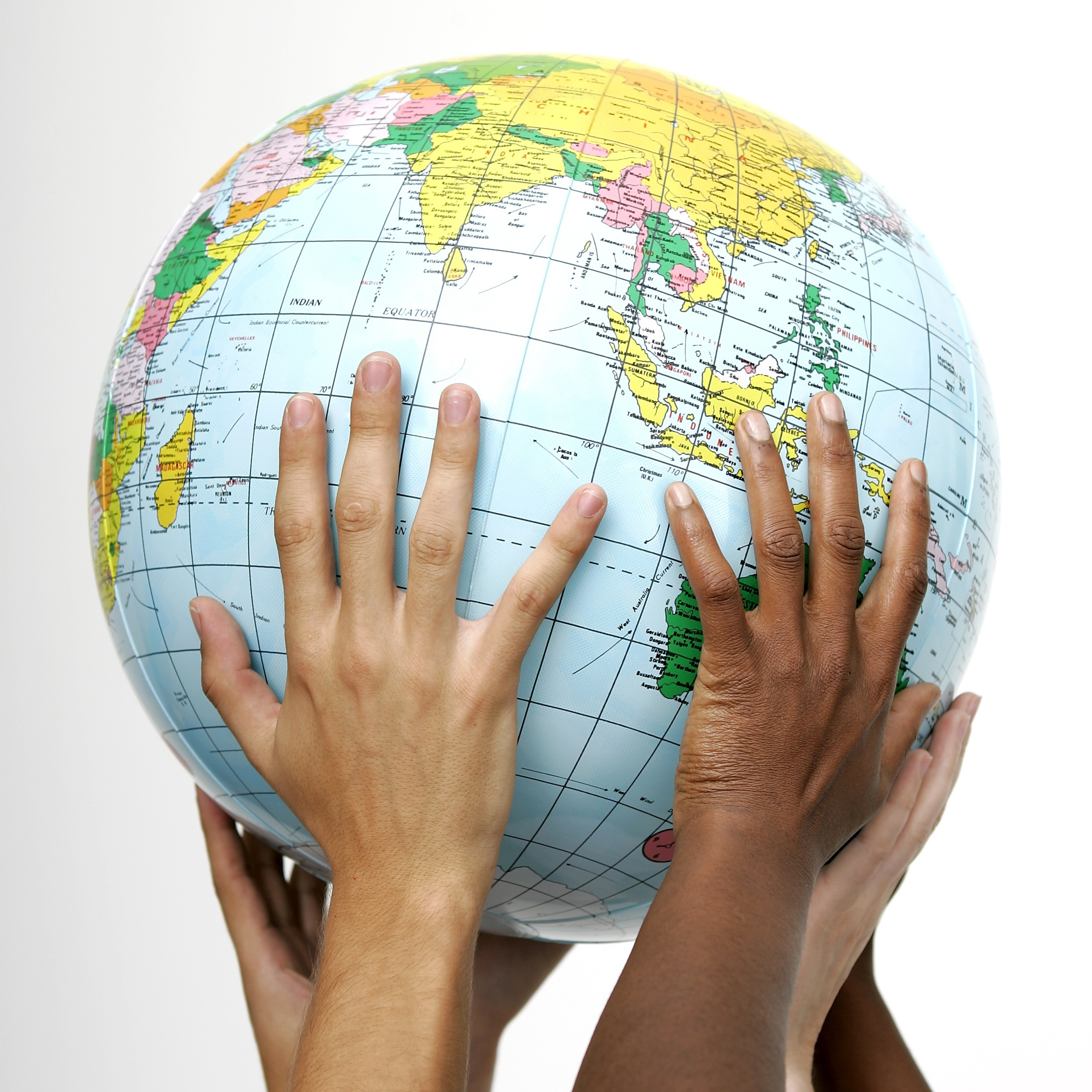 Five different children's hands raising up a globe
