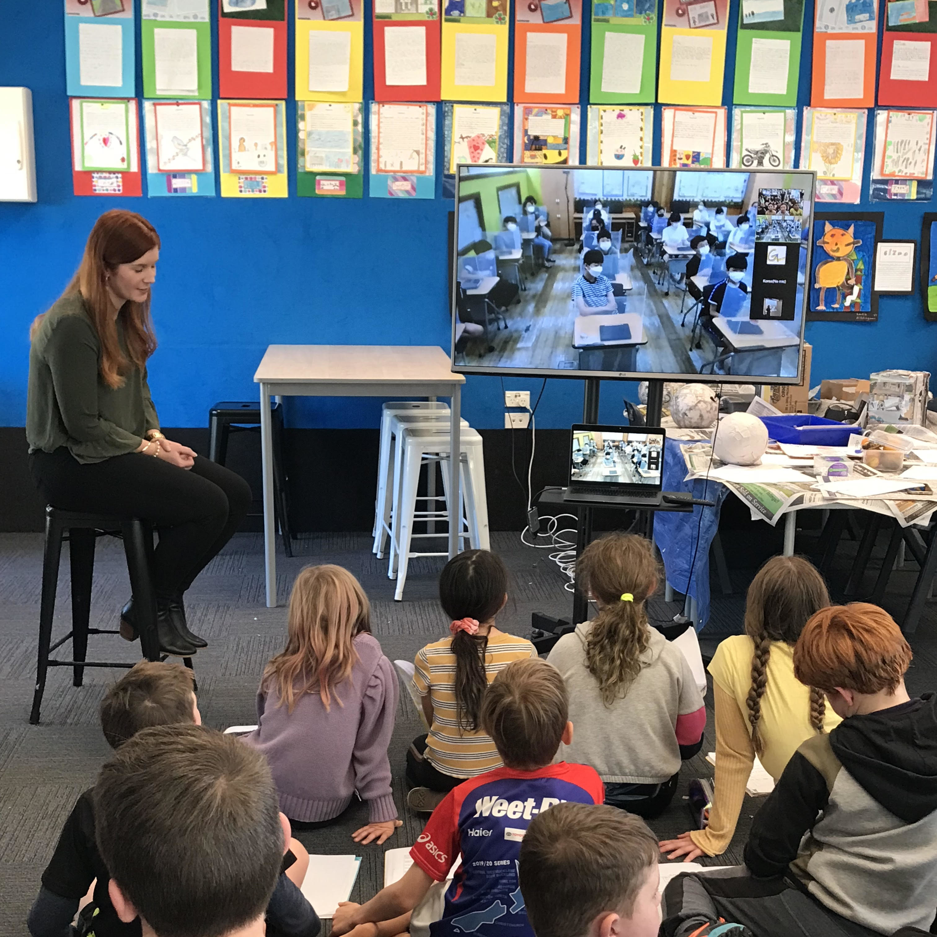 A wide shot of students in a NZ classroom connecting via zoom with their peers in a Korean classroom