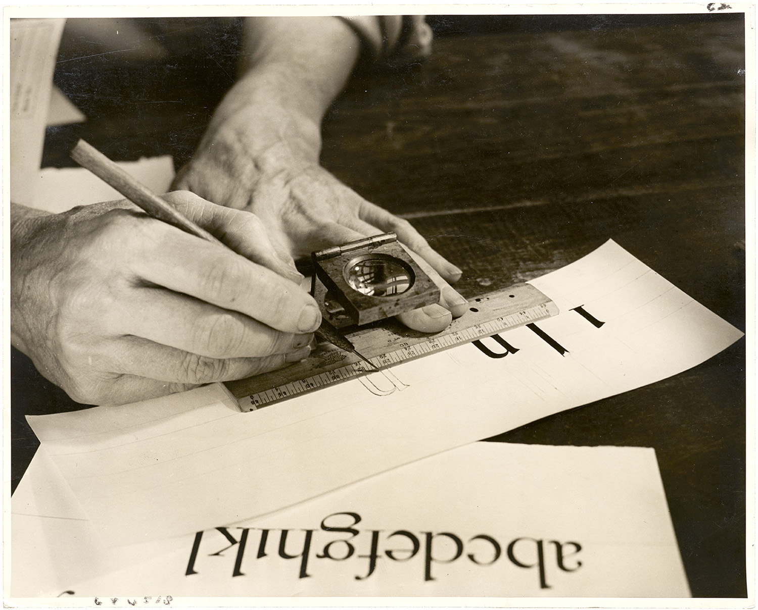 Dwiggins drawing letters using a loupe and a ruler