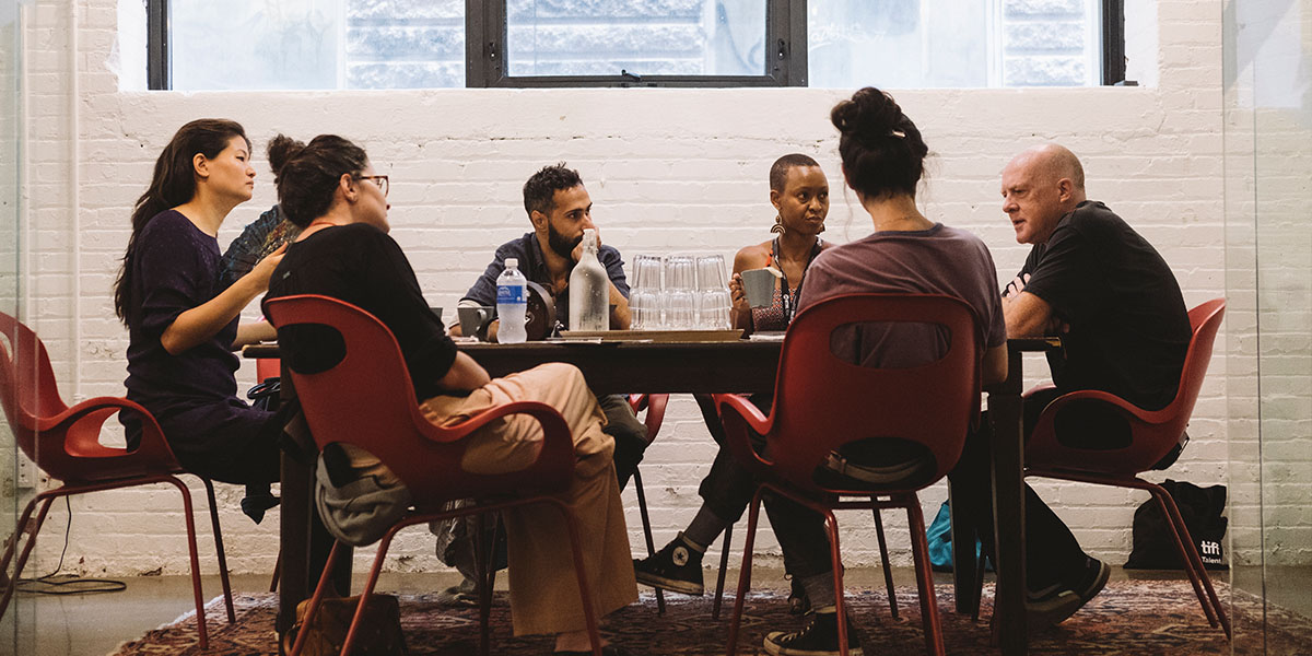 A group of people sitting around a table having a discussion.