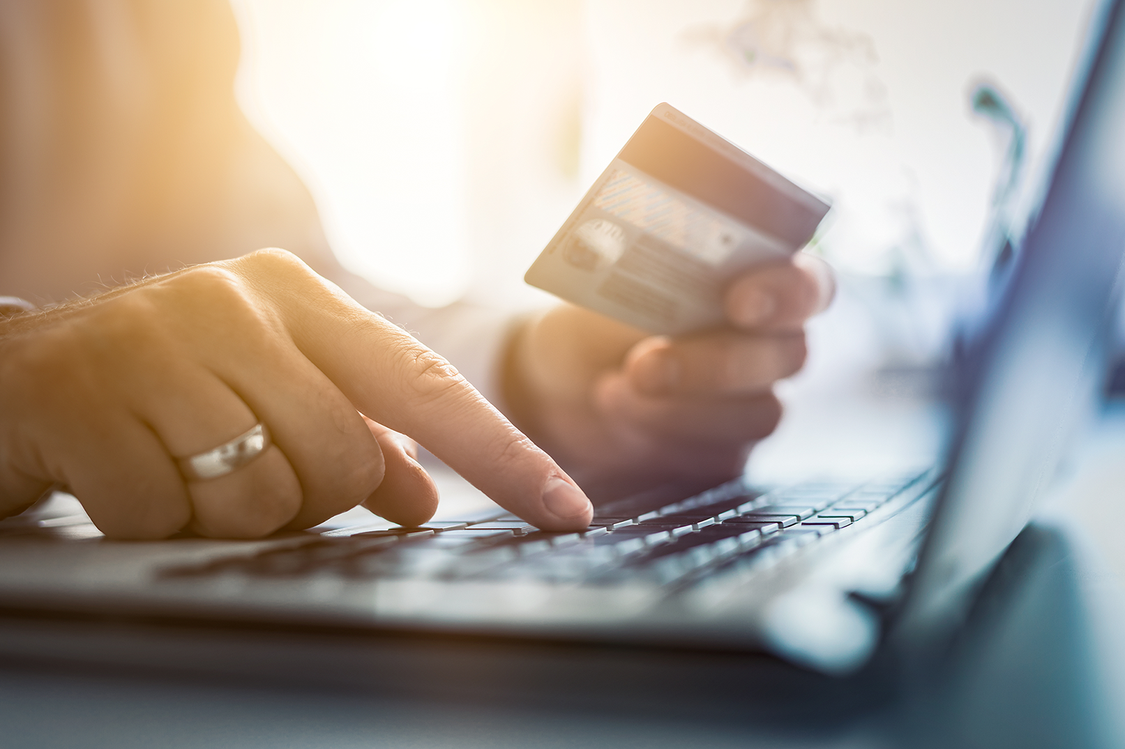 An image of a consumer using his credit card to buy online