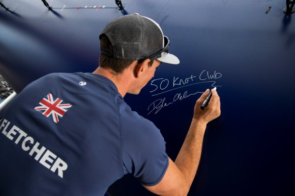 Dylan Fletcher signs the hull of the British F50 to commemorate the 50 knot barrier being broken today on the Solent.