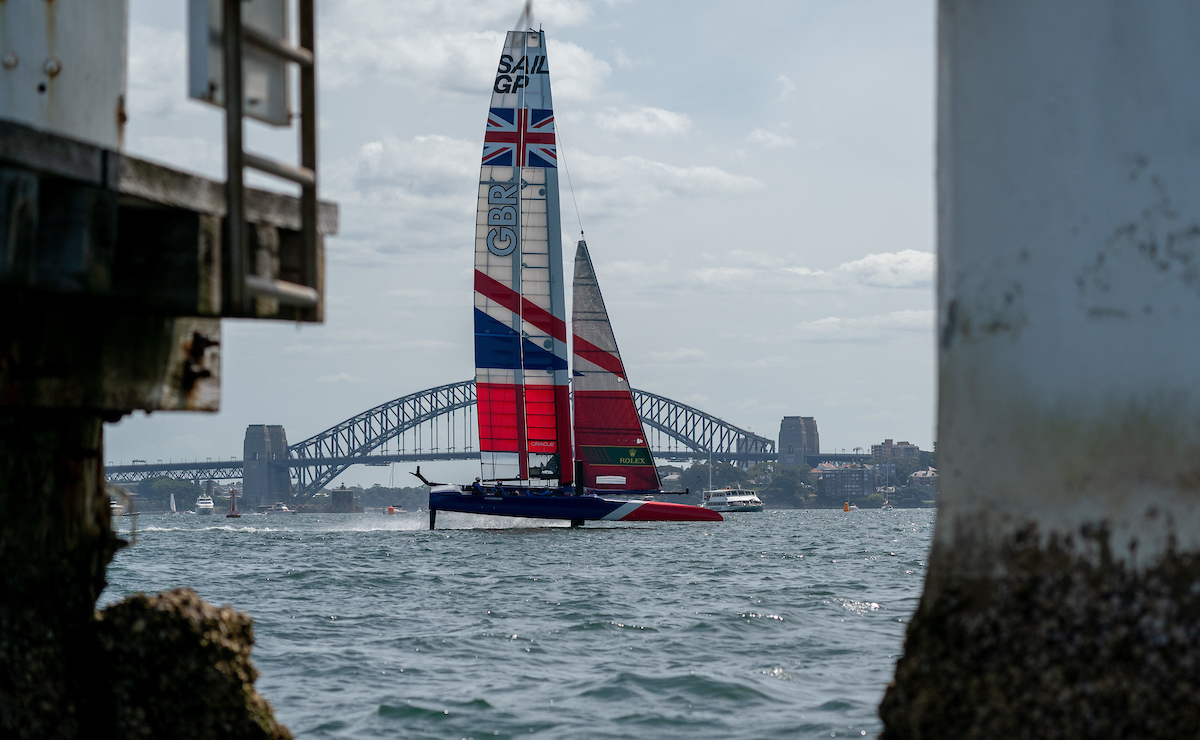 Great Britain SailGP Team skippered by Dylan Fletcher sails past a small lighthouse off of Shark Island