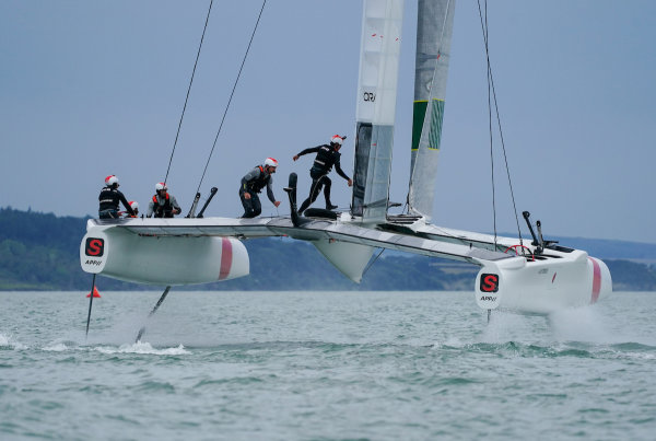 Grinders Leo Takahasi and Tim Morishima run across the catamaran as Japan SailGP Team practise on The Solent
