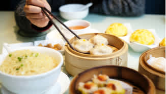 Person eating Chinese dumplings and dim sum with chopsticks at Cantonese restaurant in London