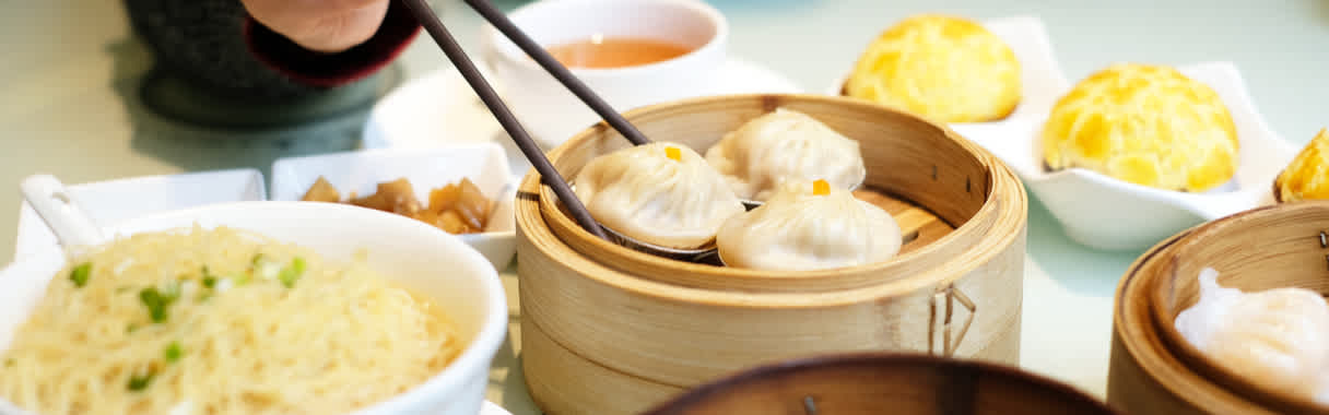 Person eating Chinese dim sum and dumplings with chopsticks at Cantonese restaurant in London