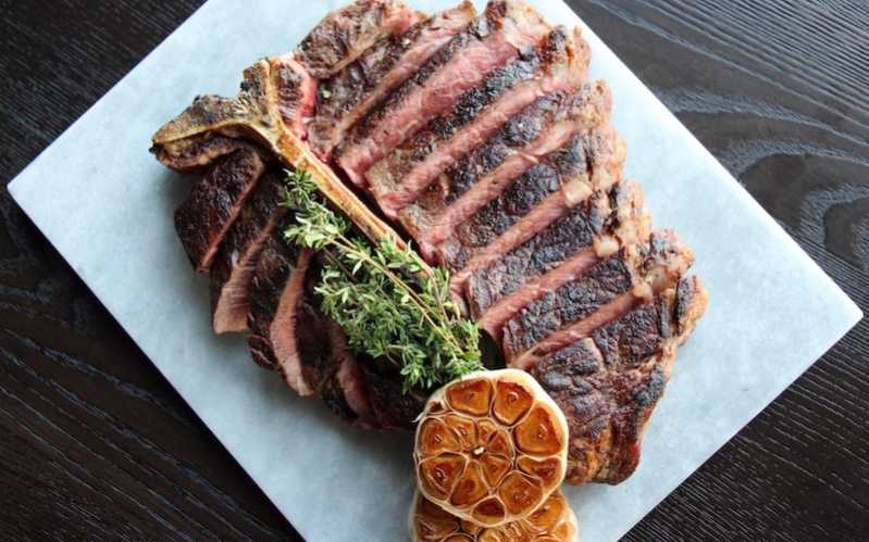 Photo of Stanbroke Black Angus Porterhouse at SKAI sliced with thyme on top