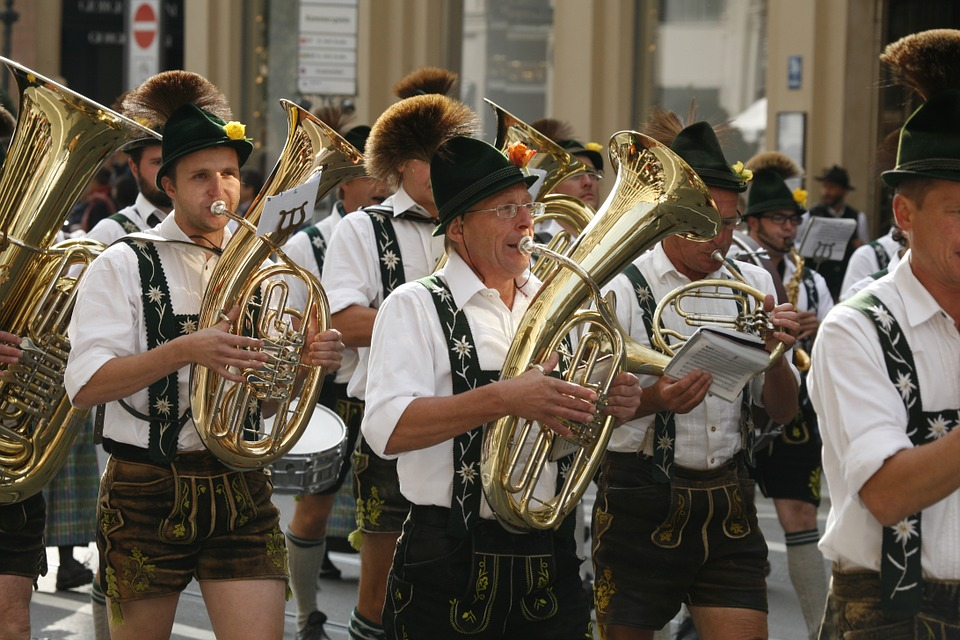 German men wearing lederhosen and marching in a band.