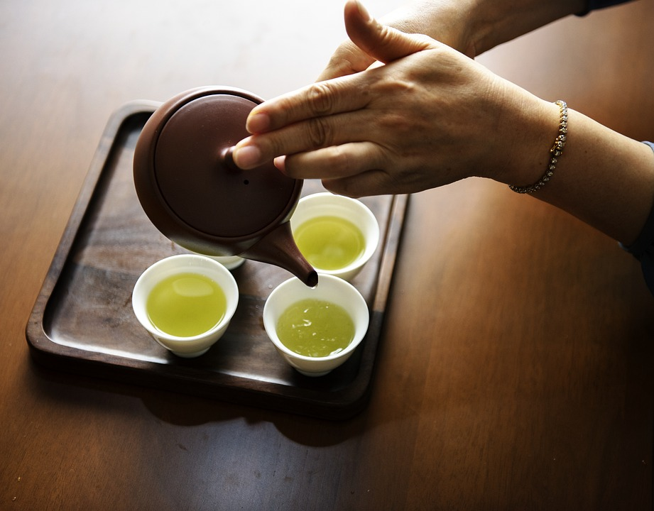 A woman preparing cups of green tea.
