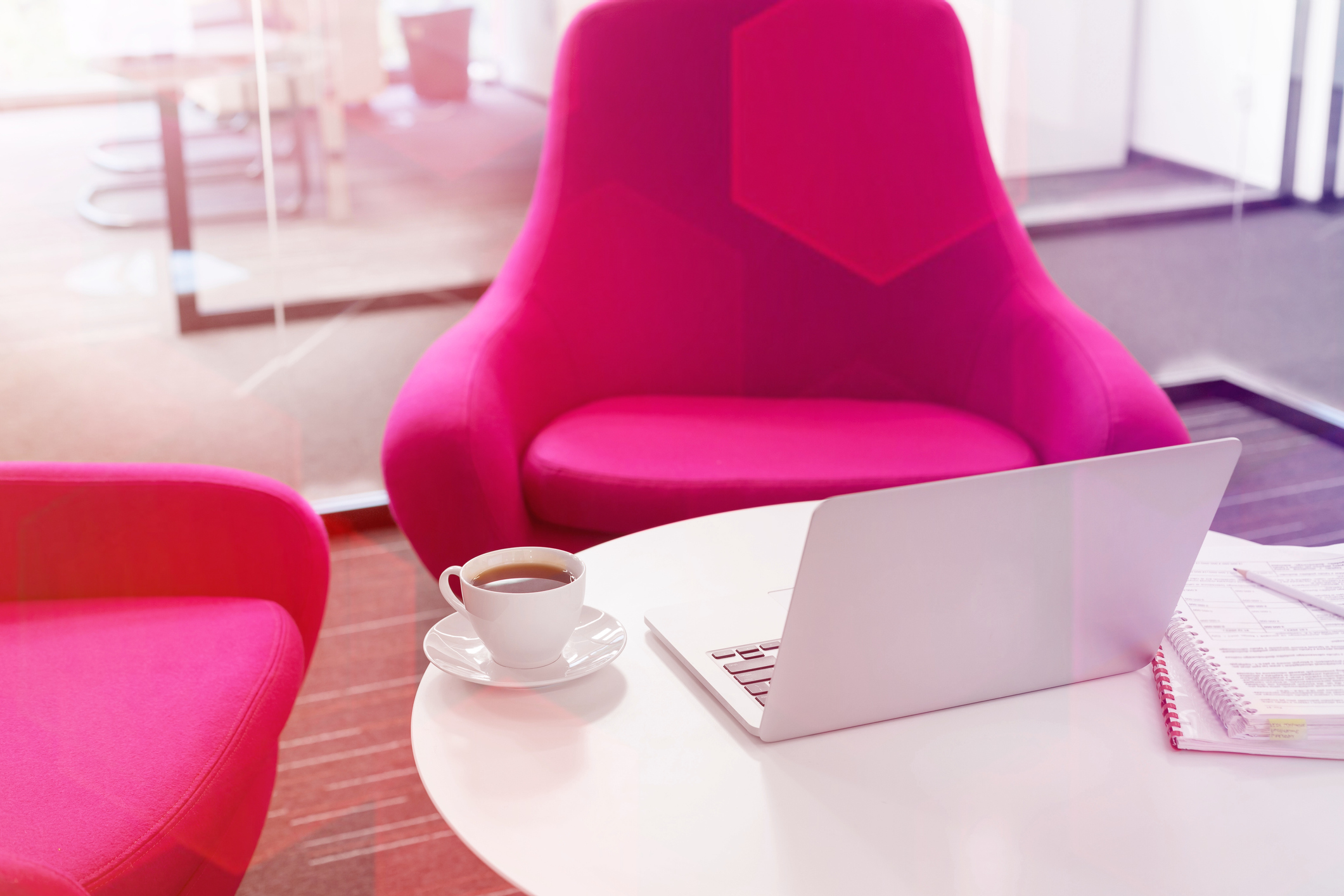 Image showing a pink couch, laptop, and coffee depicting Mesmer's comfortable environment. See our open positions.